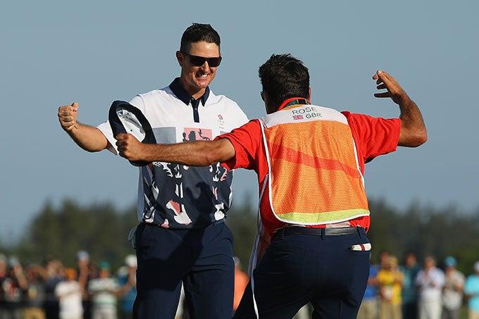 Justin Rose celebrates with his caddie, Mark Fulcher.