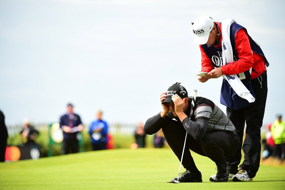 Henrik Stenson crouches to read a putt during the final round of the British Open.
