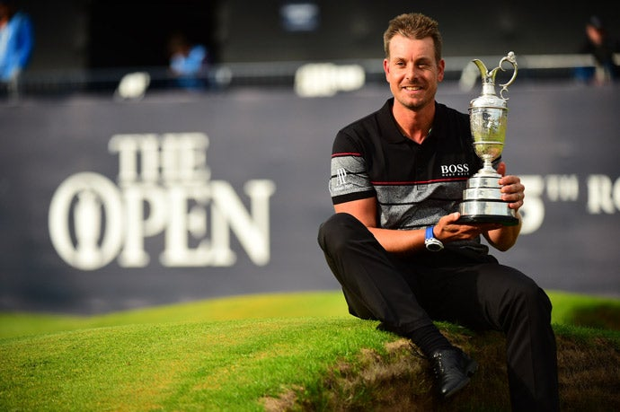The champion poses with the claret jug.