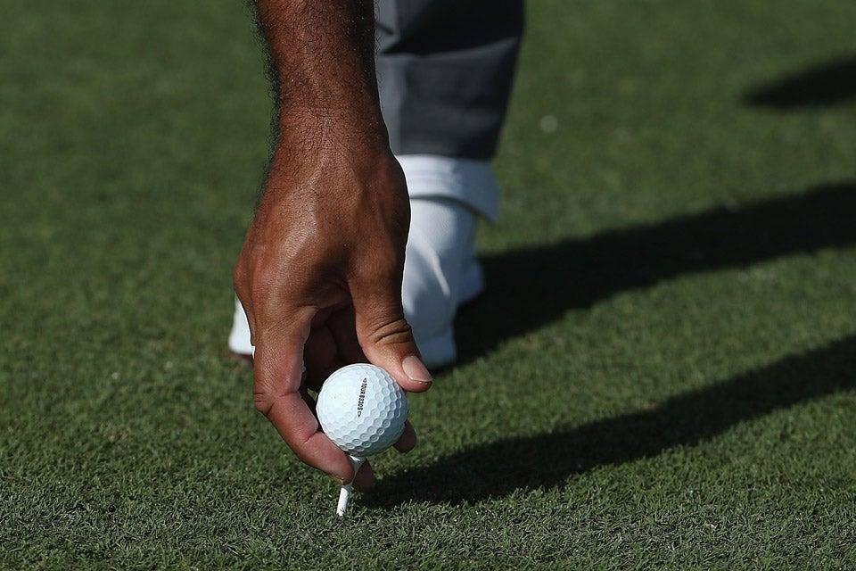 Woods tees up his new Bridgestone golf ball on Wednesday.