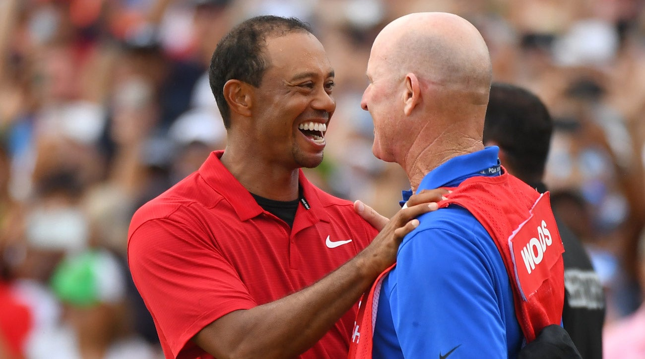 Tiger Woods shares a moment with caddie Joe LaCava after winning the 2018 Tour Championship.