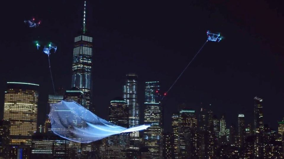 A floating net suspended by drones with the Manhattan skyline as a backdrop.