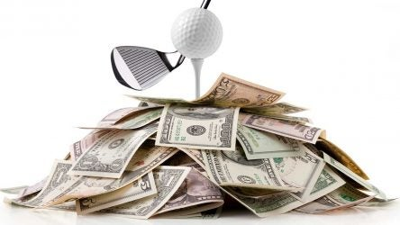 Large stack of money with golf ball on top.