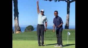 Tiger Woods and a young student from his foundation celebrate a putt they made with a robotic golf ball.