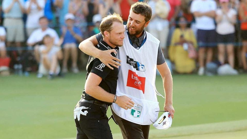 Danny Willett walks off the green with his caddie.