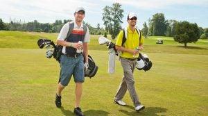 Two golfers walk across the green.