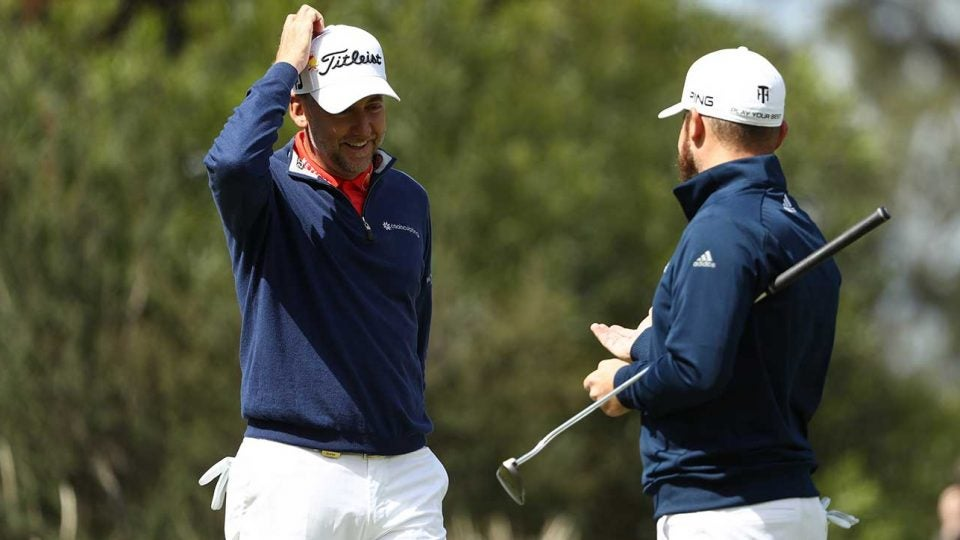 Ian Poulter and Tyrrell Hatton chat after a shot on Thursday.