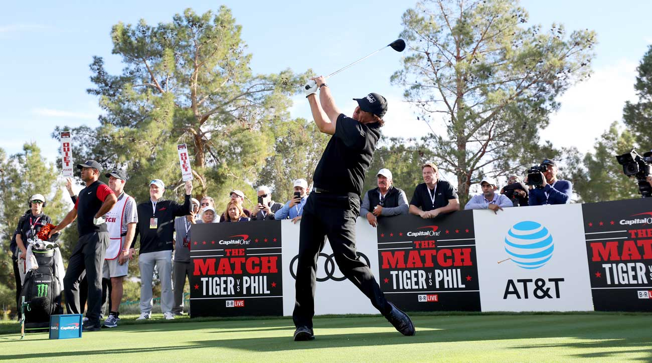 Phil Mickelson tees off during The Match as Tiger Woods looks on.