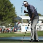 Vijay Singh pumps his fist after making a putt.