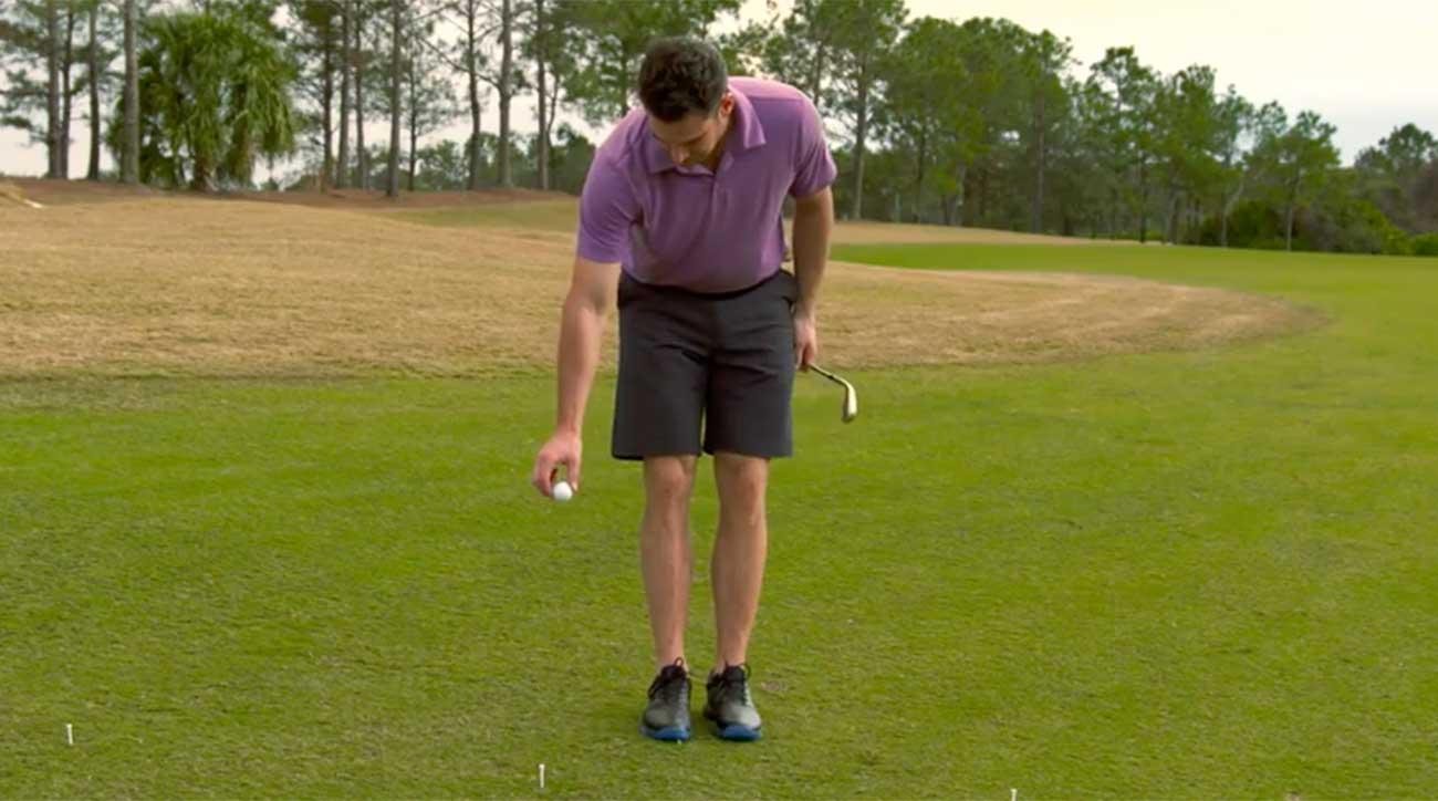 A golfer drop's a golf ball at his knees.