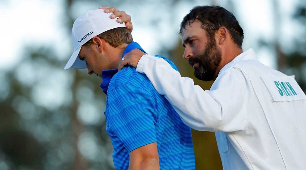 Spieth's caddie, Michael Greller, consoles him at the 2016 Masters.