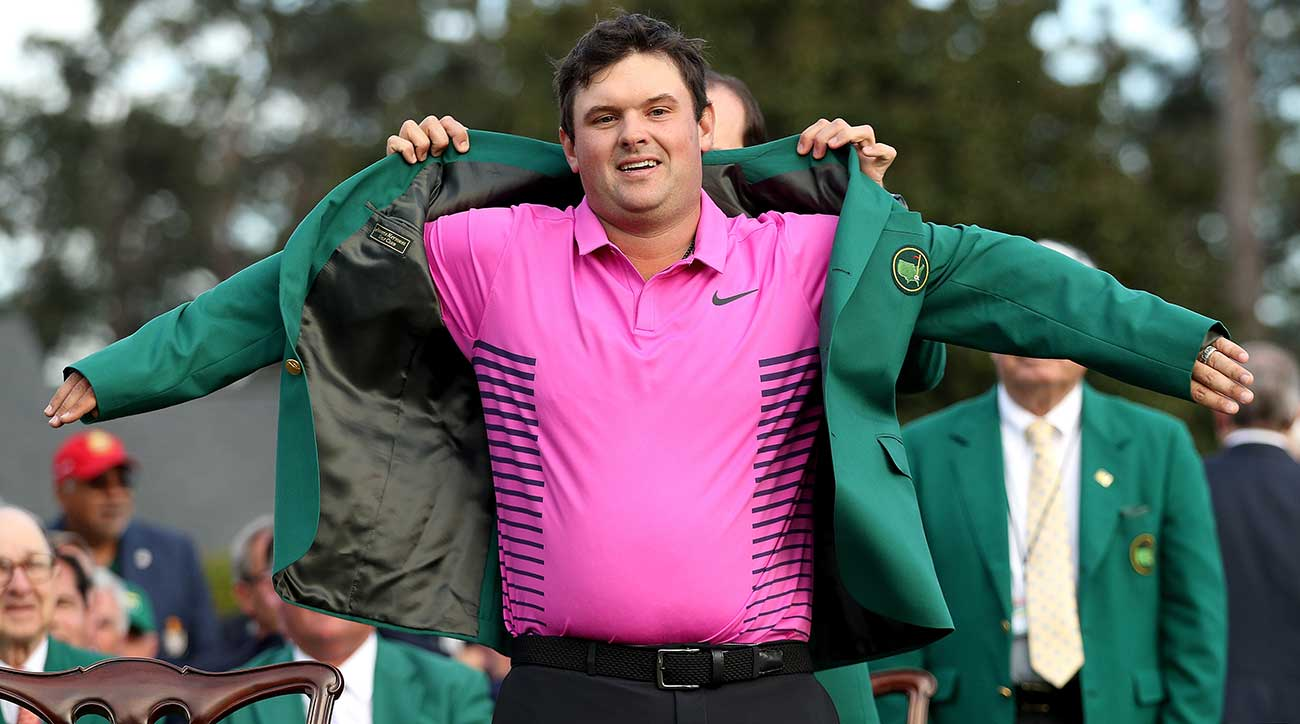 Patrick Reed slips on his Masters jacket at Augusta National.