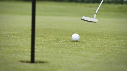 A golfer rolls a putt toward the hole.