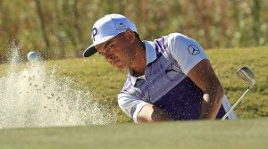 Rickie Fowler hits out of a bunker.