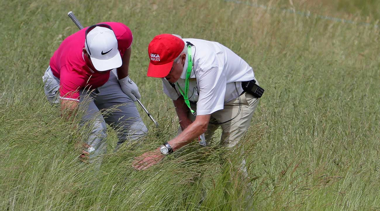 Jason Day and a USGA official search for a golf ball.