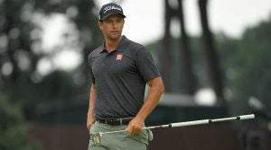 Adam Scott looks over a putt.
