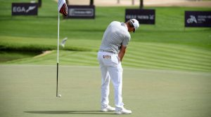 Bryson DeChambeau putts with the flagstick in during the first round of the Dubai Desert Classic