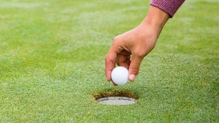 A golfer places a ball in the golf hole.