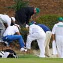 Caddies and officials search for a golf ball at the Masters.