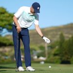 Jordan Spieth makes a drop with Slugger White looking on at the 2019 Sony Open.