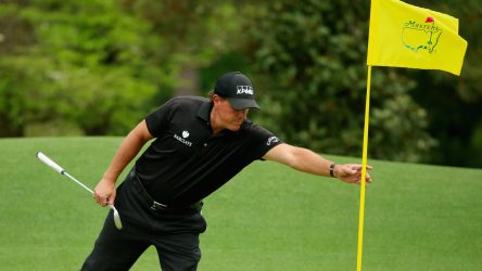 Phil Mickelson tends a flagstick during the final round of the 2015 Masters