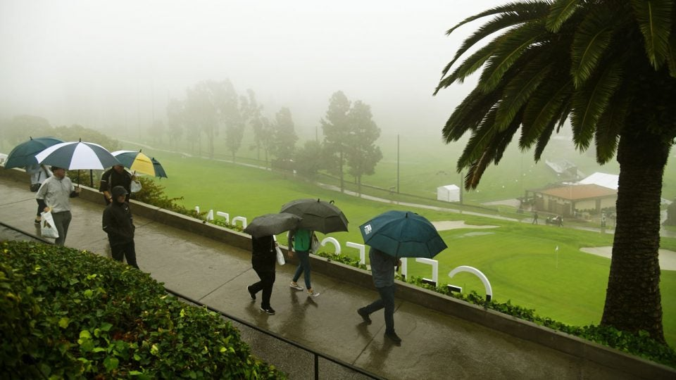 People take cover from rain under umbrellas Thursday at the 2019 Genesis Open
