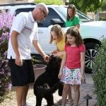 The Kahn family (Amelia, left; Makenzie, right) with Pongo, who is being trained as a service dog to help the girls.
