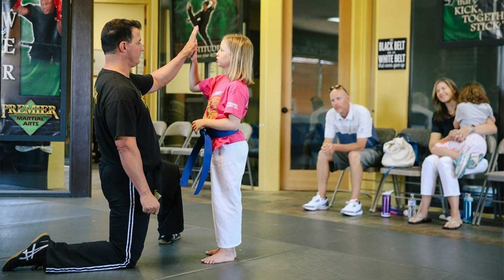 Amelia works with her martial arts instructor as her parents and sister look on.
