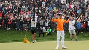 Rickie Fowler raises his arms after winning the Waste Management Phoenix Open.