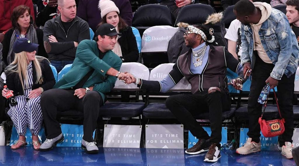 Patrick Reed and his wife, Justine, greet rapper 2 Chainz during a Knicks game last Spring.