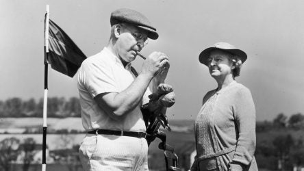 irca 1945: Full-length image of an elderly man and woman standing on a golf course beside the pin, as the man lights a cigar. The woman stands with a bag of clubs. (Photo by Harold M. Lambert/Lambert/Getty Images)