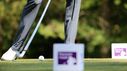 Golfer teeing off between tee markers