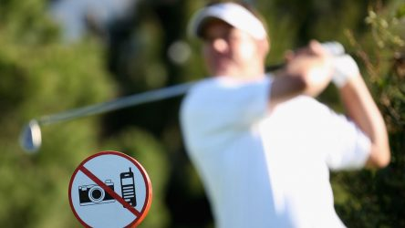 """Golfer in backswing with """"no phones or cameras"""" sign in background"""