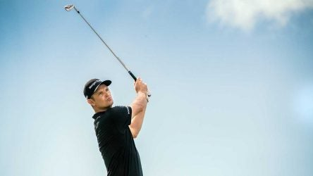 Justin Rose takes a swing and looks down the fairway.