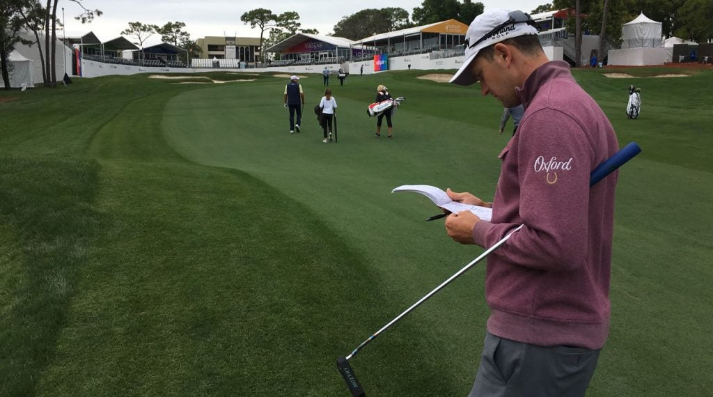 Trainer consults his yardage book at the Valspar Championship, with Steve Stricker and his wife and daughter in the background.