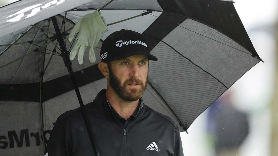 Dustin Johnson holds an umbrella during the final round of the Players Championship.