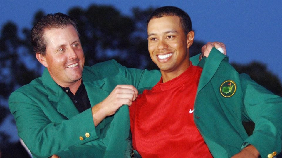 Phil Mickelson puts the Masters green jacket on Tiger Woods.
