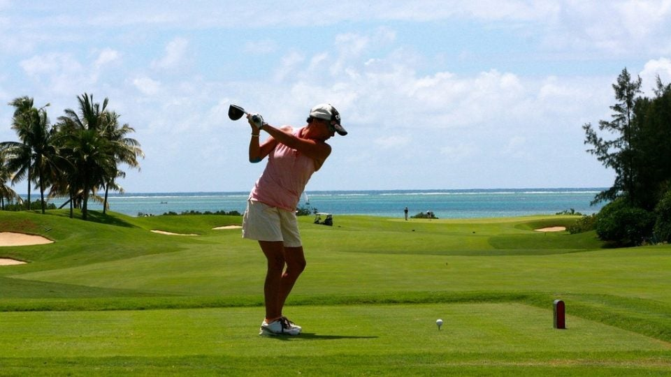 Woman on the beach answering how to hit a golf ball