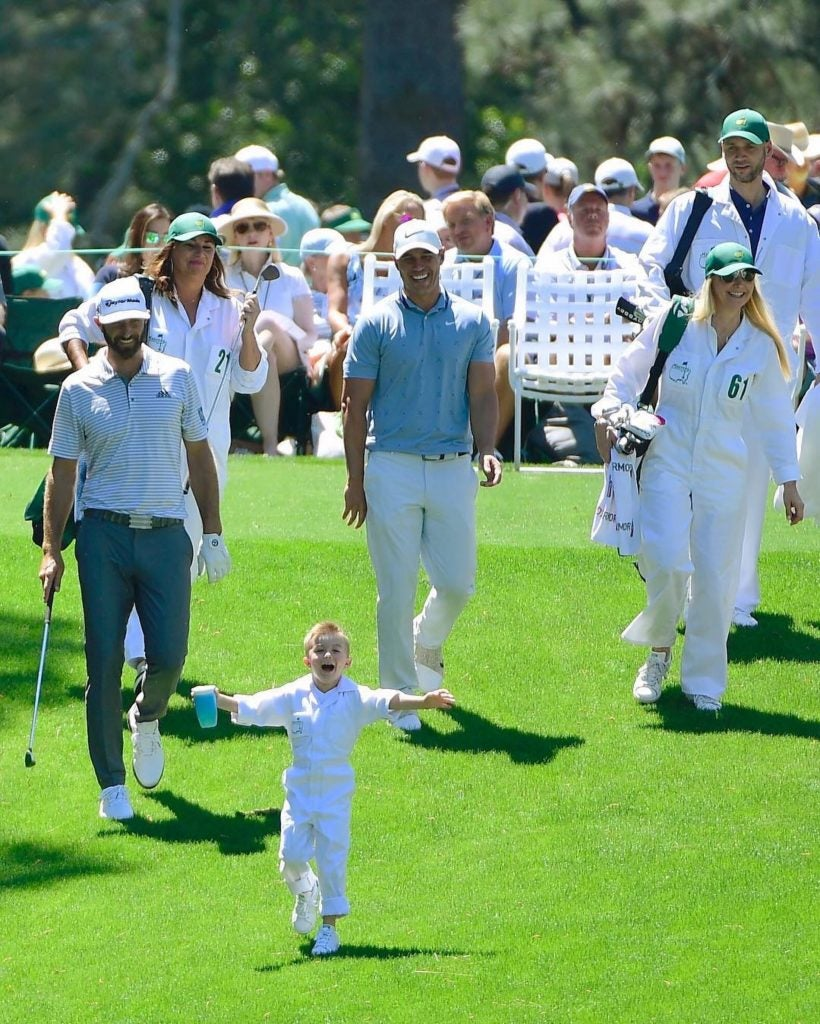 Dustin Johnson and Brooks Koepka come down the fairway together following a kid.