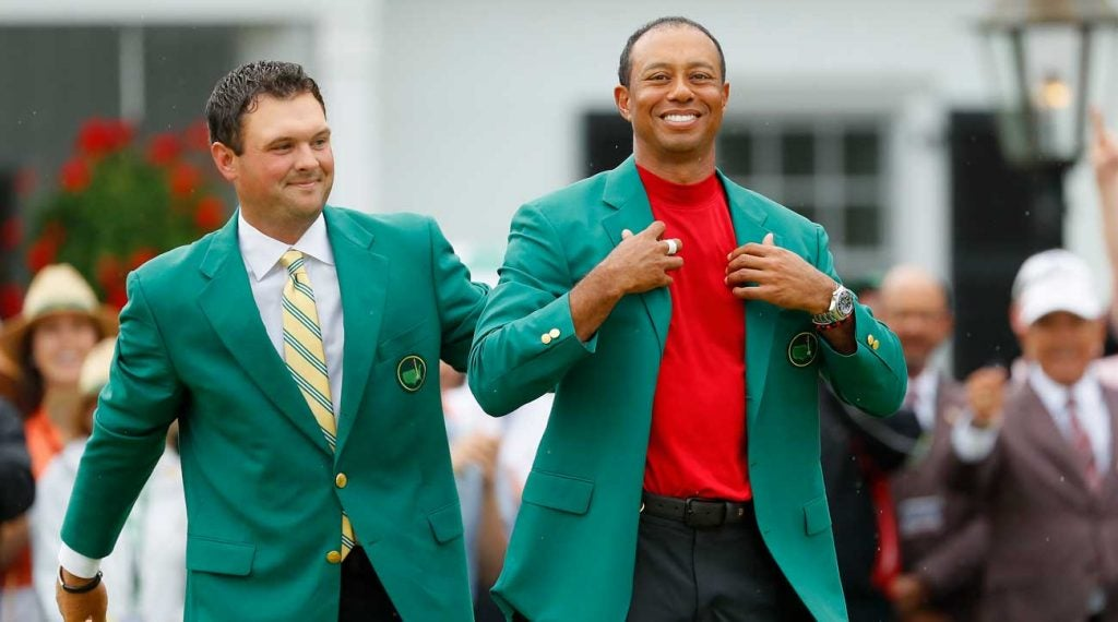 Patrick Reed helps fit Tiger Woods with a fifth green jacket.
