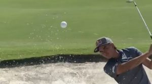 Rickie Fowler splashes out of a bunker.