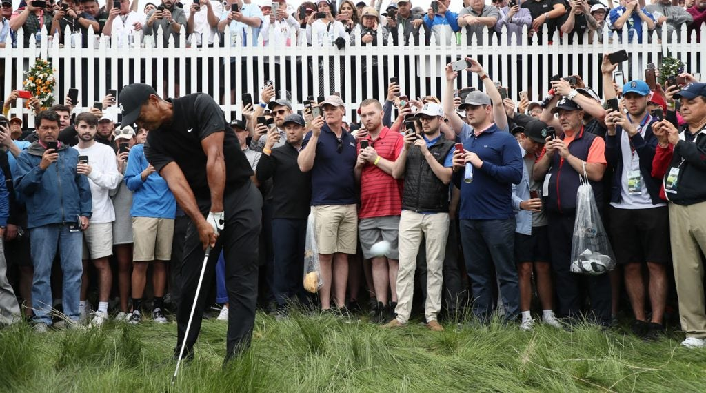 Tiger Woods takes a mighty swing from the heavy rough on the first hole at Bethpage Black.