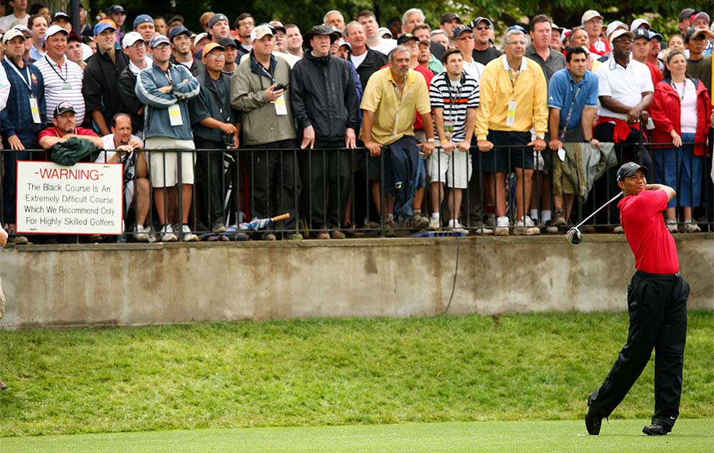 Tiger Woods tees off during the final round of the 2009 U.S. Open at Bethpage Black, with the sign just feet away from him.