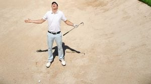 Man in golf course bunker.