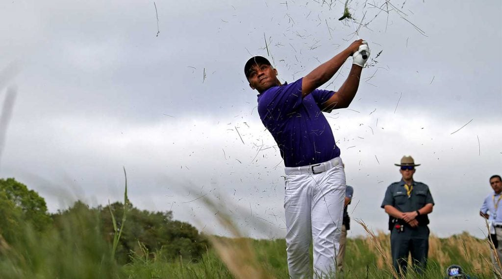 Harold Varner III hacks out of the rough during the 2019 PGA Championship.