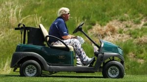 John Daly rides a cart during the first round of the 2019 PGA Championship.