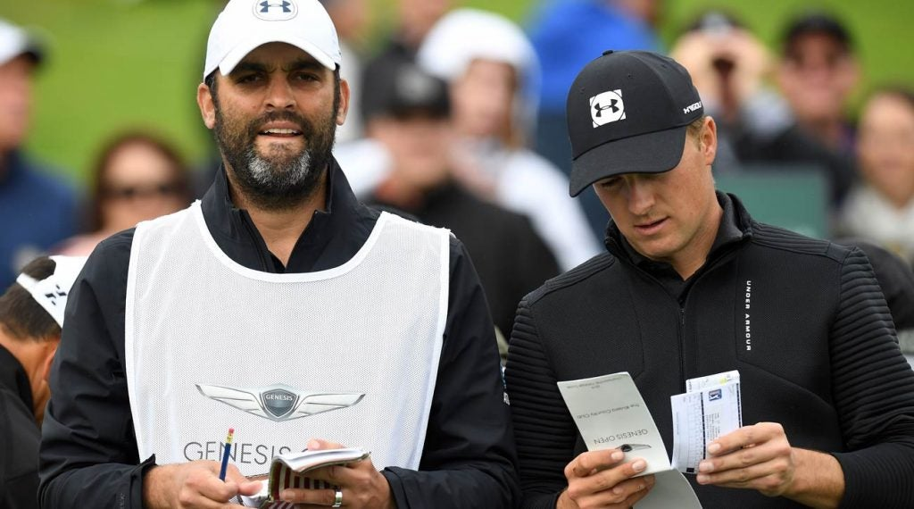 Jordan Spieth consults with his caddie, Michael Greller, at the 2019 Genesis Open.