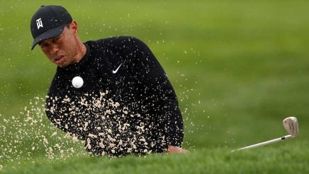 Tiger Woods blasts out of a bunker during a practice round at Bethpage Black on Tuesday.