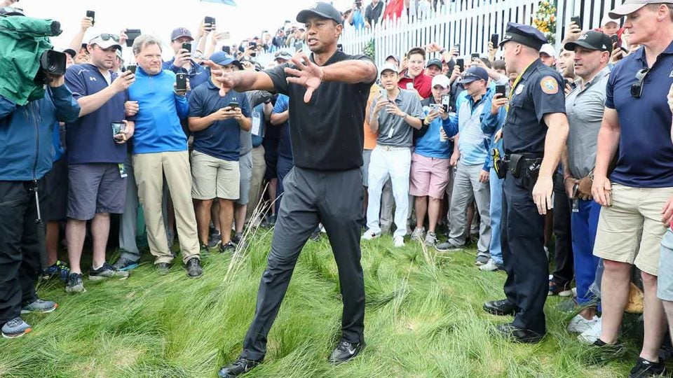 Tiger Woods tries to clear a path to the hole during his second round of the PGA Championship.