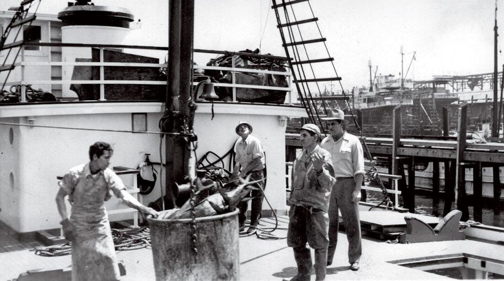 Al Santos (far right), conducting business on his fishing boat.